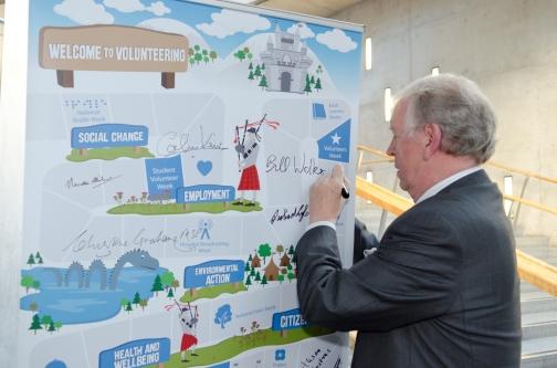 Bill Walker MSP signs community volunteering campaign banner