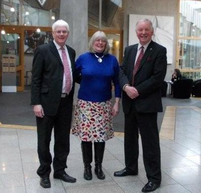 Rev Dr Martin Scott (left), Rev Jayne Scott and Bill Walker MSP in the Scottish Parliament Garden lobby